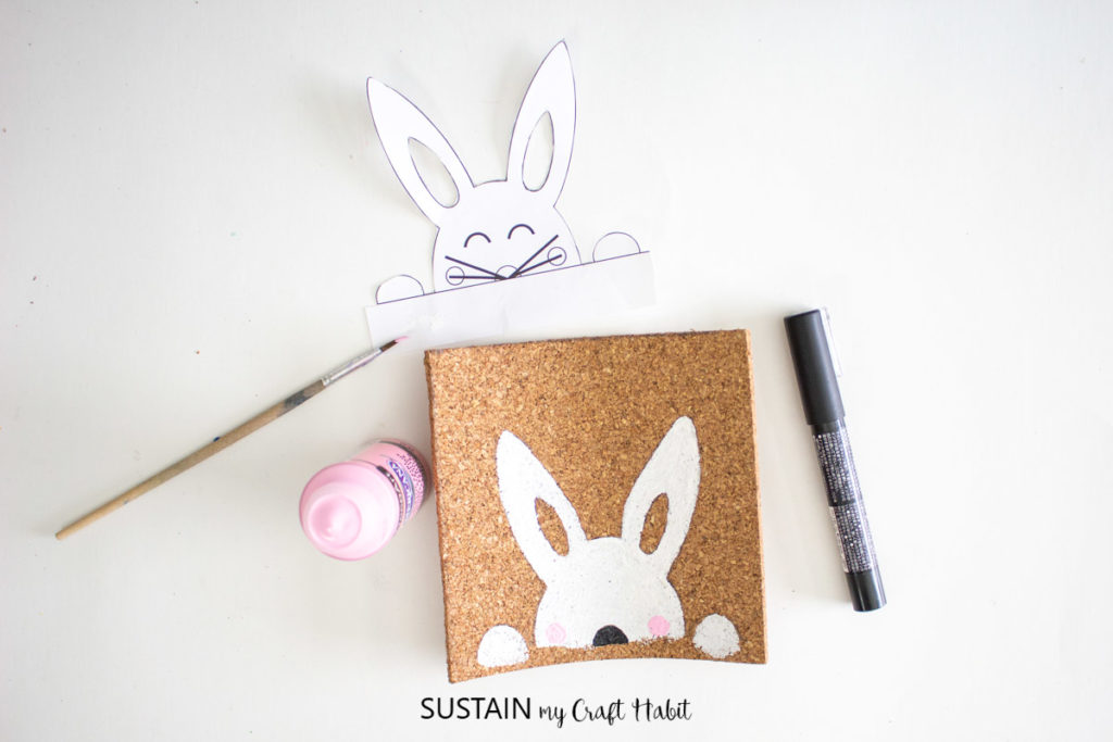 Adding pink cheeks to the painted bunny.