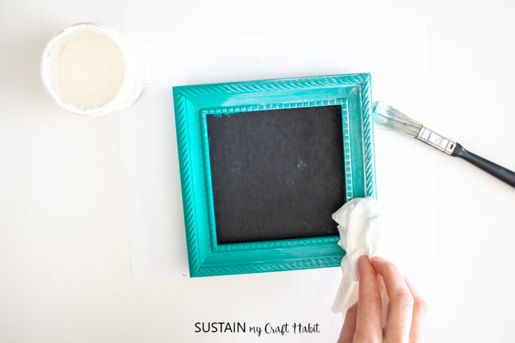Rubbing wax with a paper towel onto a picture frame.