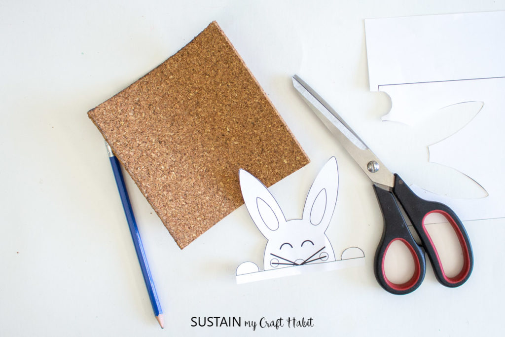 Cut out Easter bunny template next to scissors, a pencil and a cork sheet.