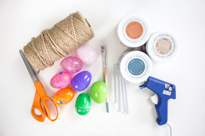 Materials needed to make twine wrapped Easter eggs, including plastic eggs, twine, scissors, paint and paint brushes.