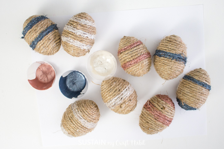 Adding stripes of paint to Easter eggs.