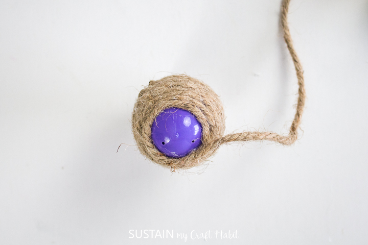 Wrapping twine around a plastic egg.