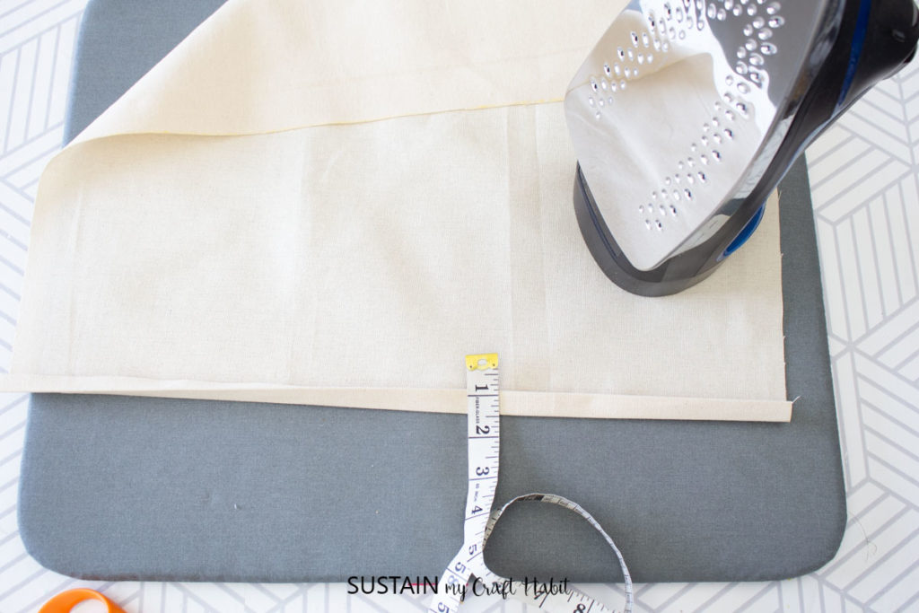 Measuring and ironing a piece of canvas.