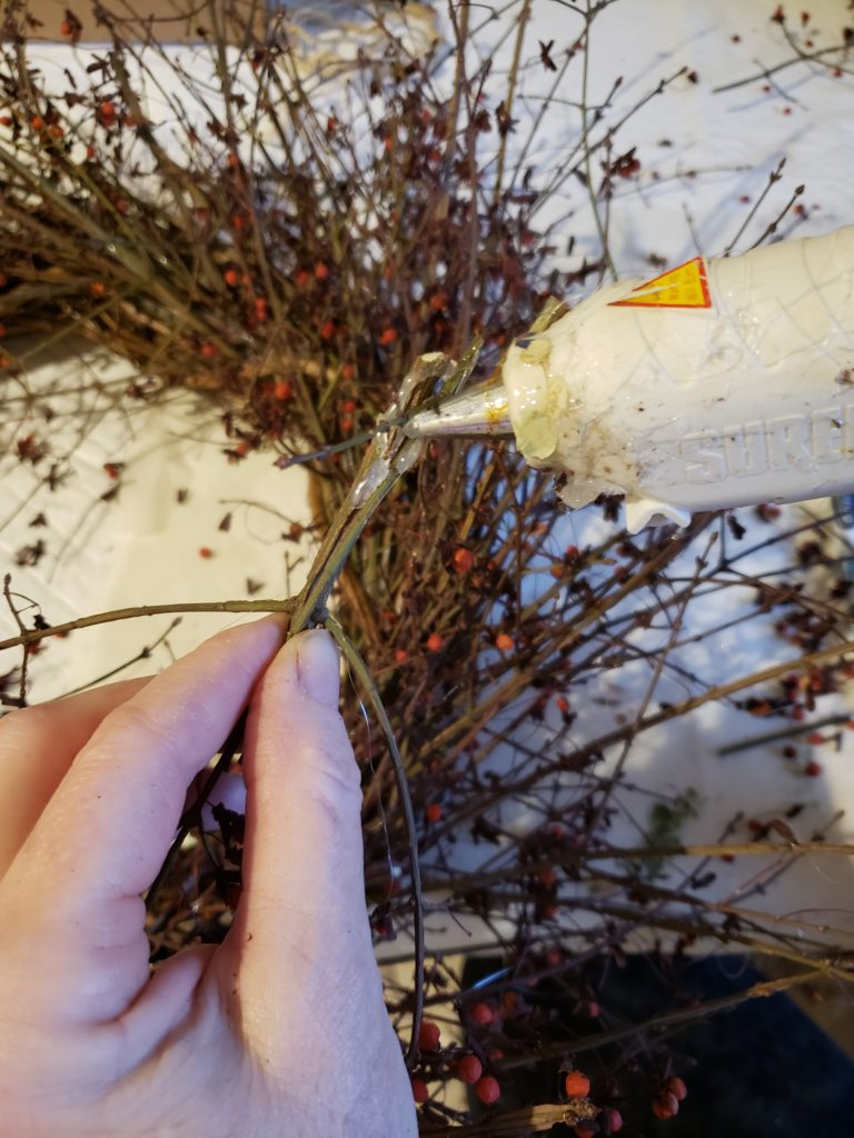glueing the loose branches on to the wreath