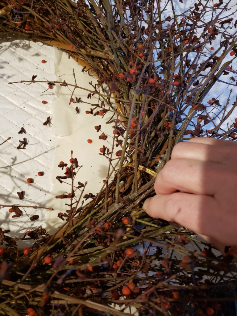 attaching the loose twigs to a grapevine wreath form.