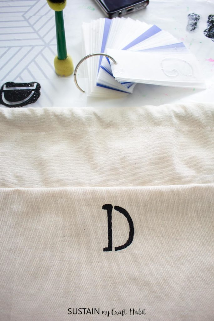 """Stencing a letter """"D"""" onto the laundry bag."""