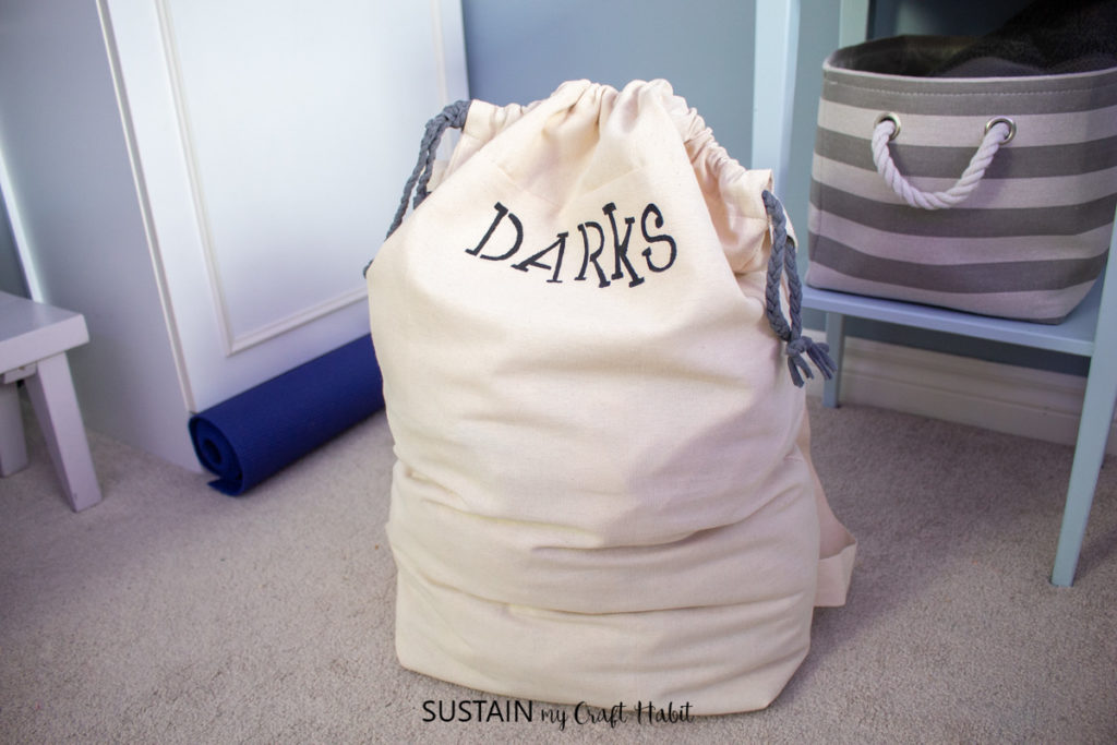 """Laundry bag with the word """"darks"""" filled with laundry."""