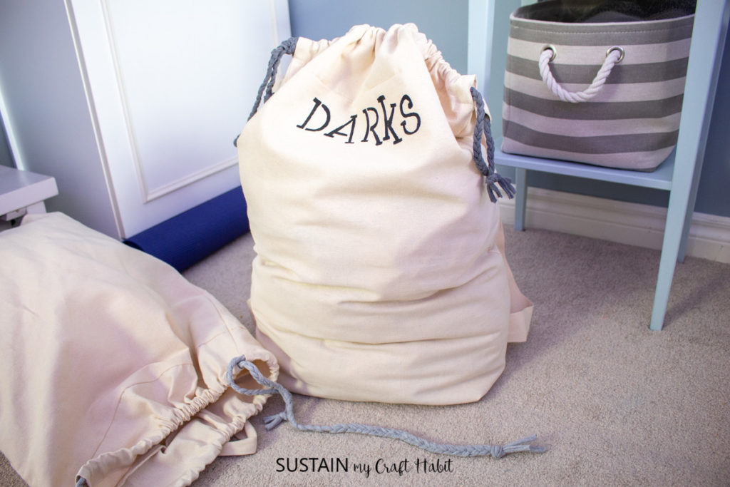 """Laundry bag with the word """"darks"""" next to a spilling bag."""