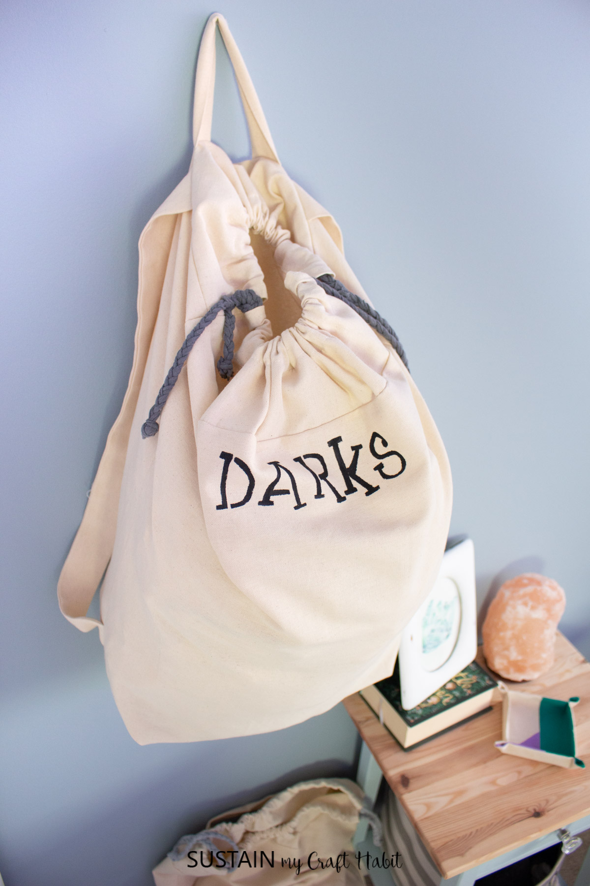 """Laundry bag with the word """"darks"""" hanging from the wall."""