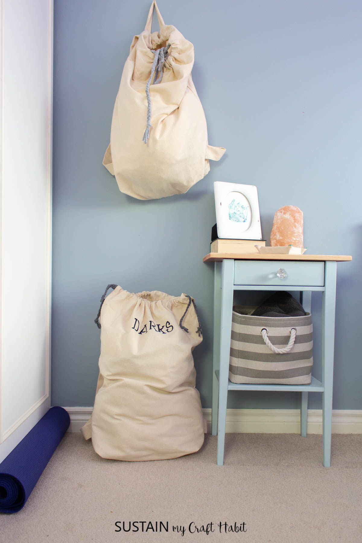 Laundry bags on the floor and hanging on a wall.
