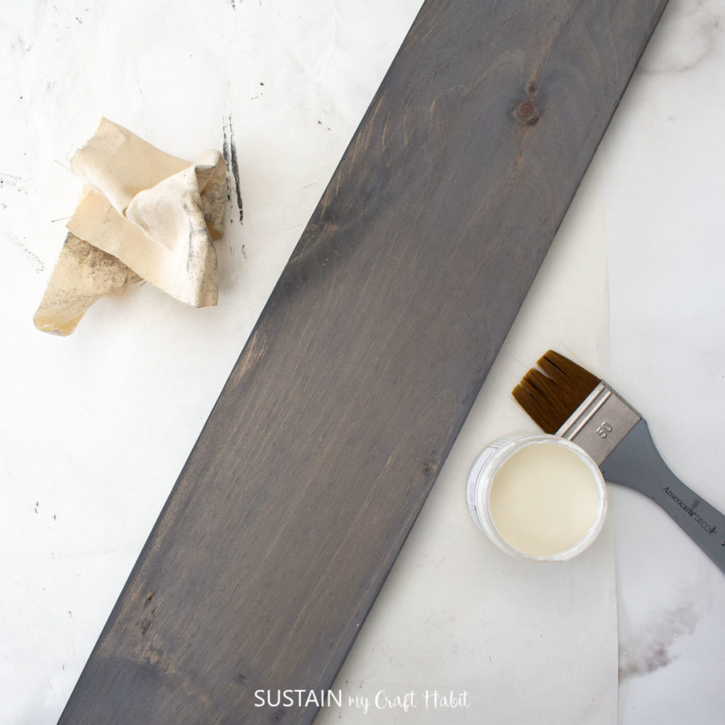 The wood pine board stained with a dark gray chalky paint.