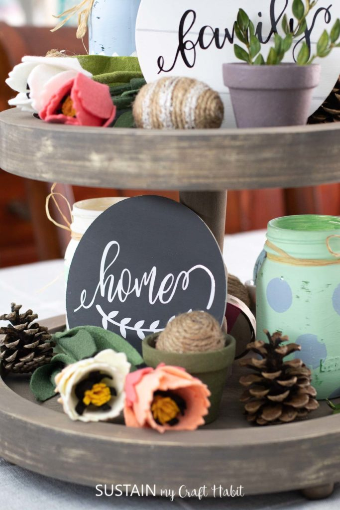 Tiered tray decorated with round wood signs, plants, flowers and Easter decor.