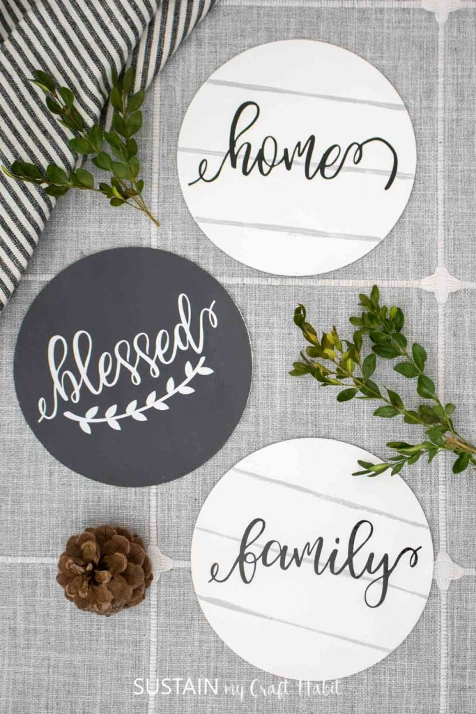 Round wood signs with vinyl lettering decorated with pine cones and greenery.