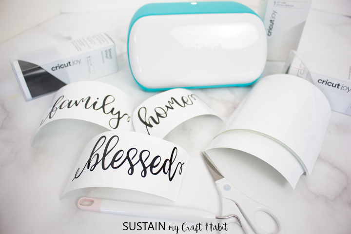 Cut pieces of transfer tape next to the cut vinyl words and Cricut Joy machine.