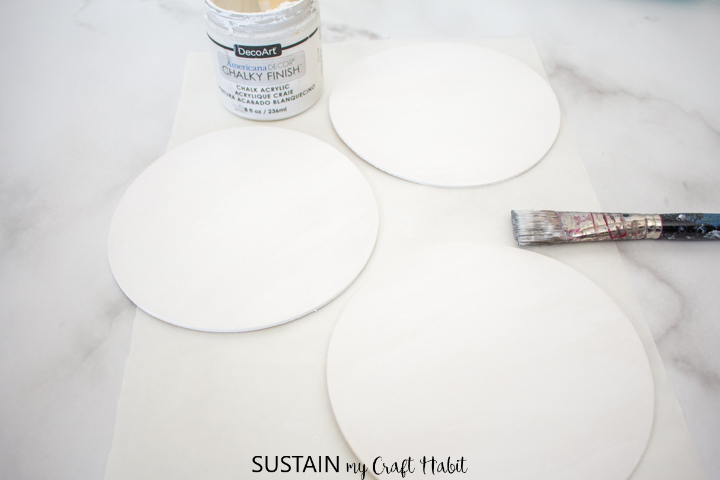 Painting one side of the wood circles with white paint.