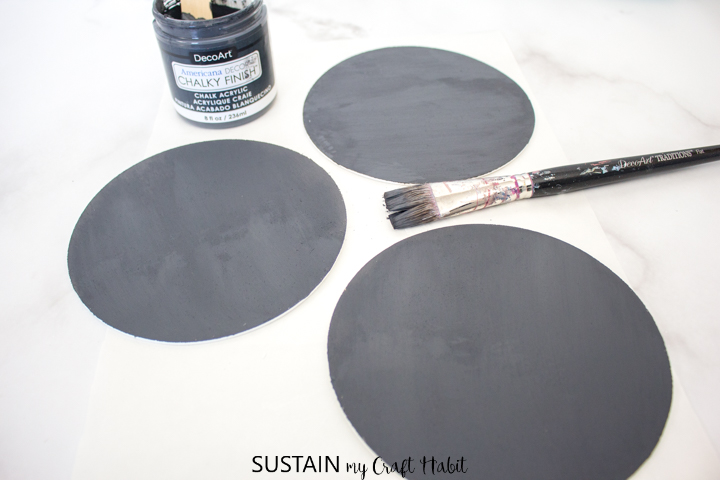 Painting the back of the wood circles with dark grey paint.