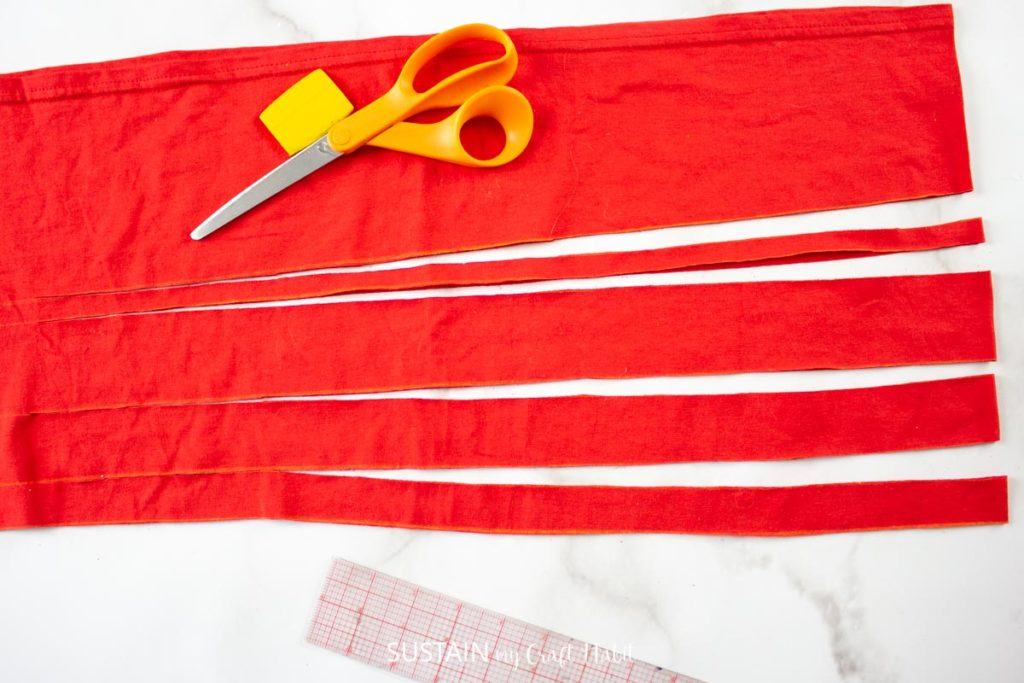 """Cutting 1"""" wide strips into the red tshirt."""