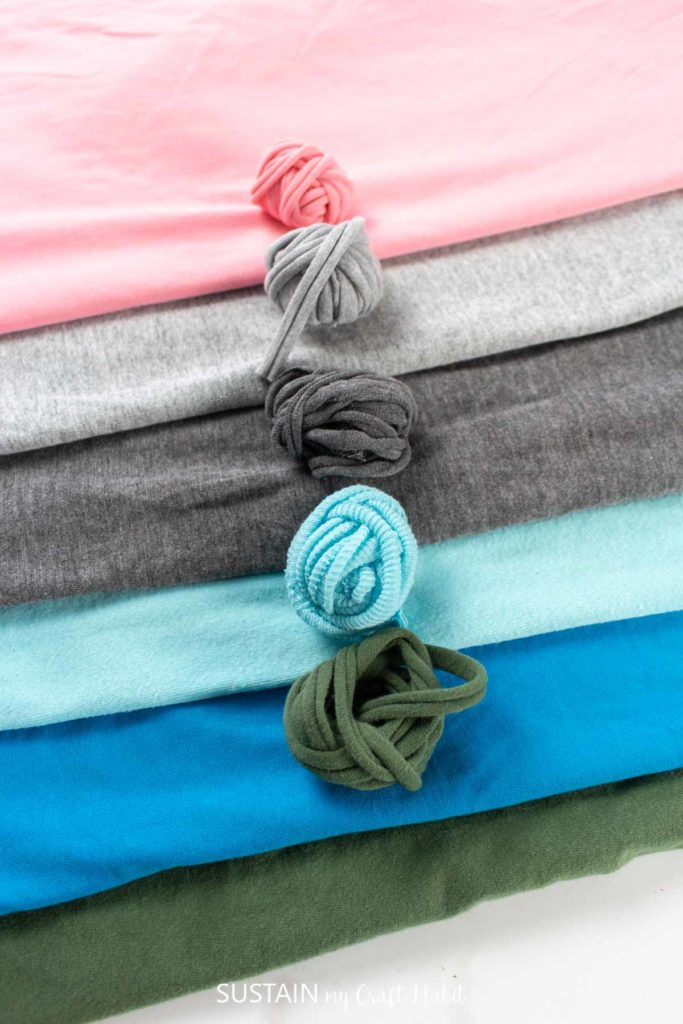 Rolled balls of tshirt yarn laying on top of shirts.