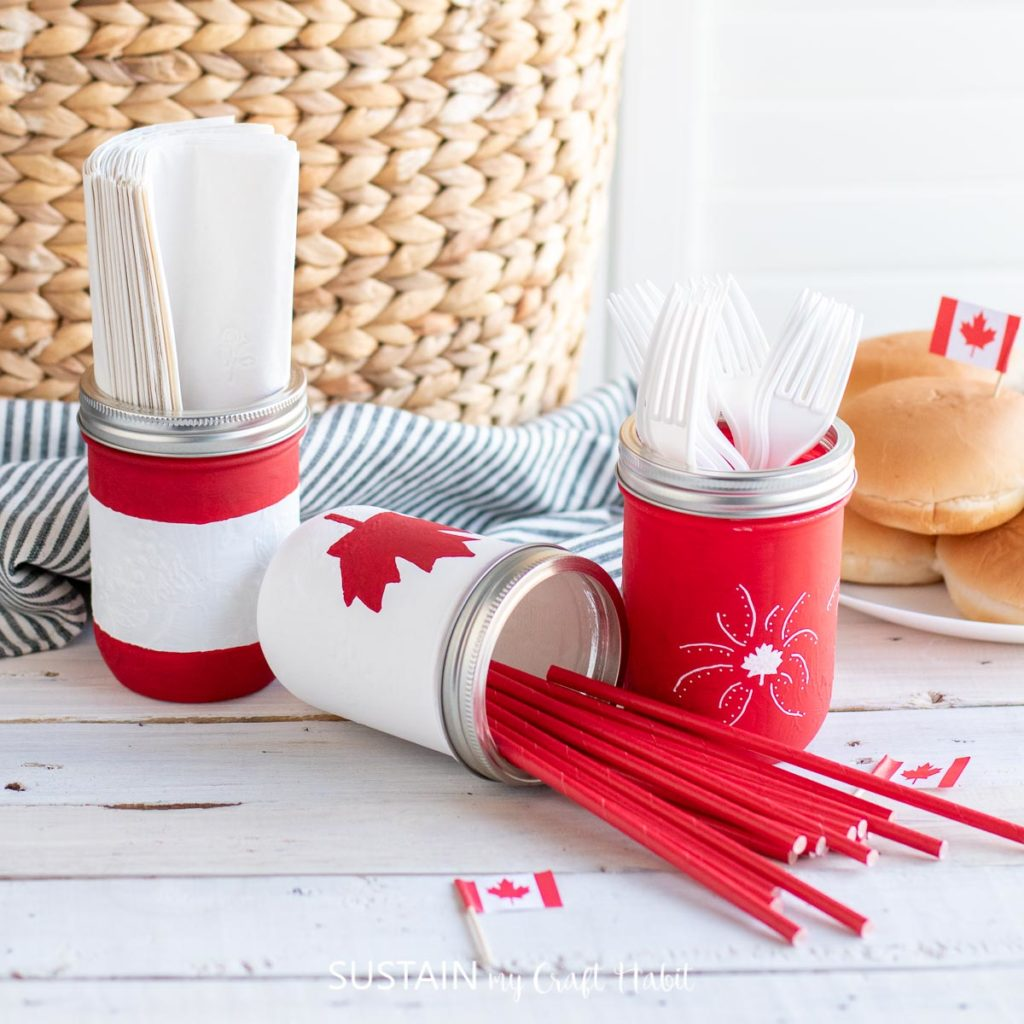 Canada Day painted mason jars filled with utensils.