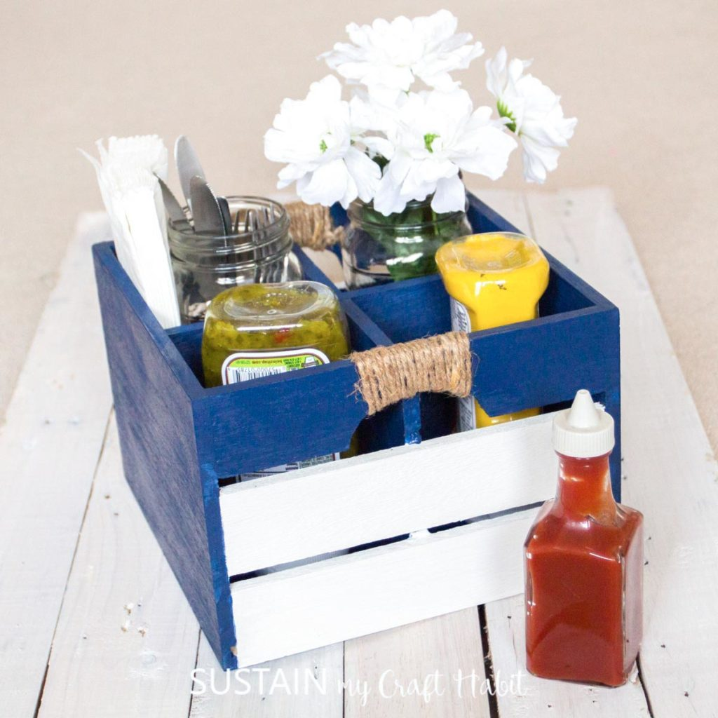 Painted BBQ caddy holding condiments, flower jar and utensils.