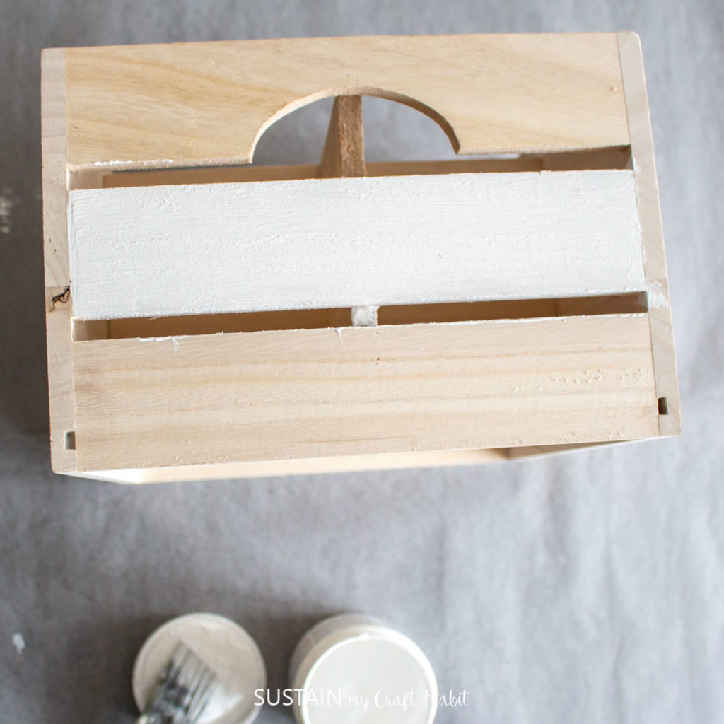 Painting one side of a wooden crate with white paint.