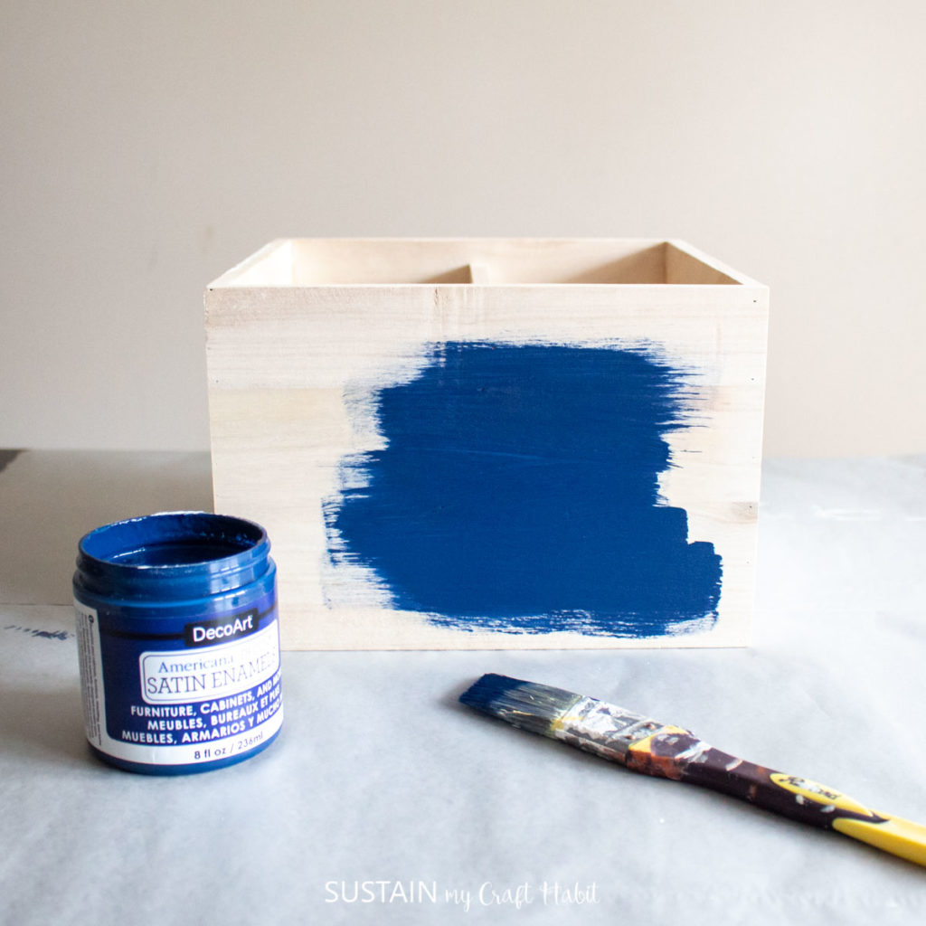 Painting the sides of a wooden crate with blue paint.
