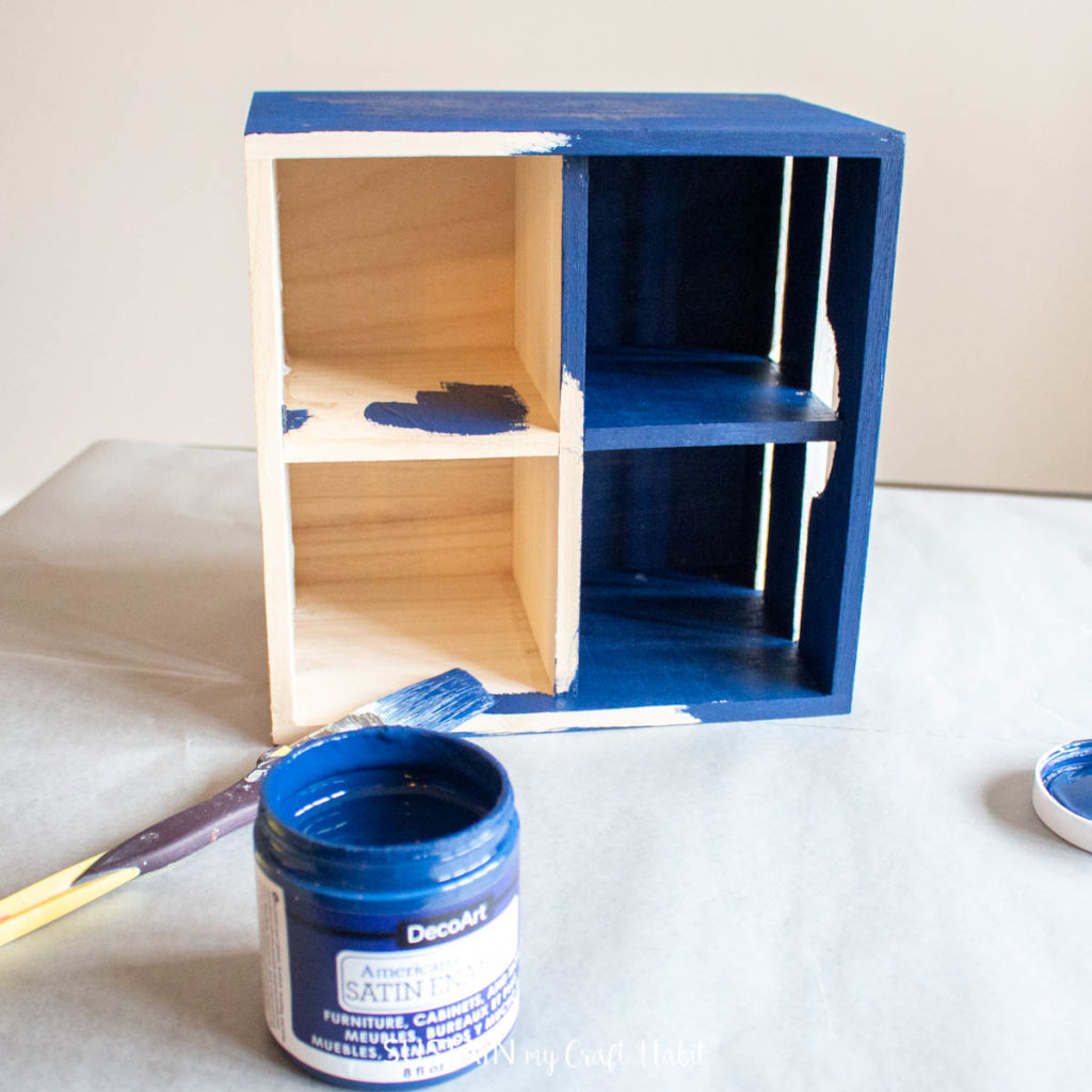 Painting the inside of the wooden crate with blue paint.