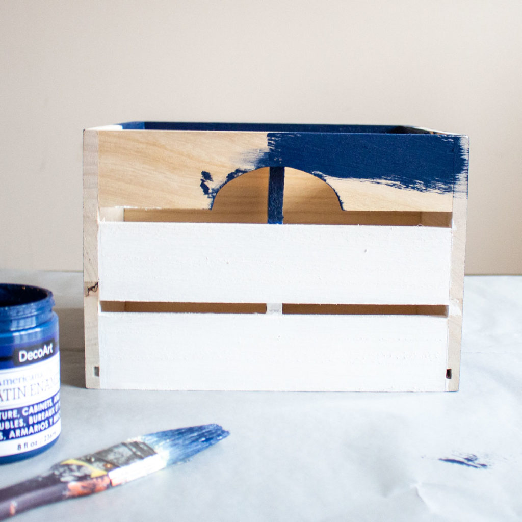 Painting the remaining sides of the wooden crate with blue paint.