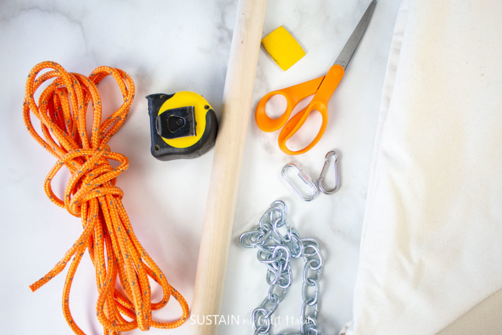 Materials such as rope, wooden dowel, measuring tape, scissors and chain.