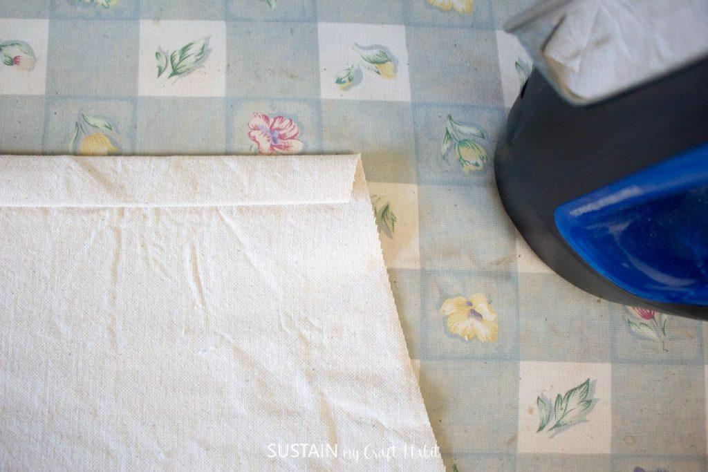 Folding over the edge of fabric.