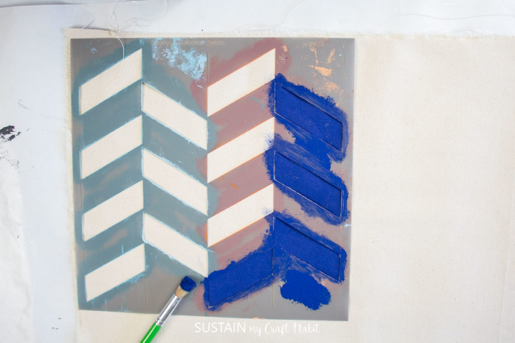 Using a zig zag stencil to paint a pattern on a fabric.