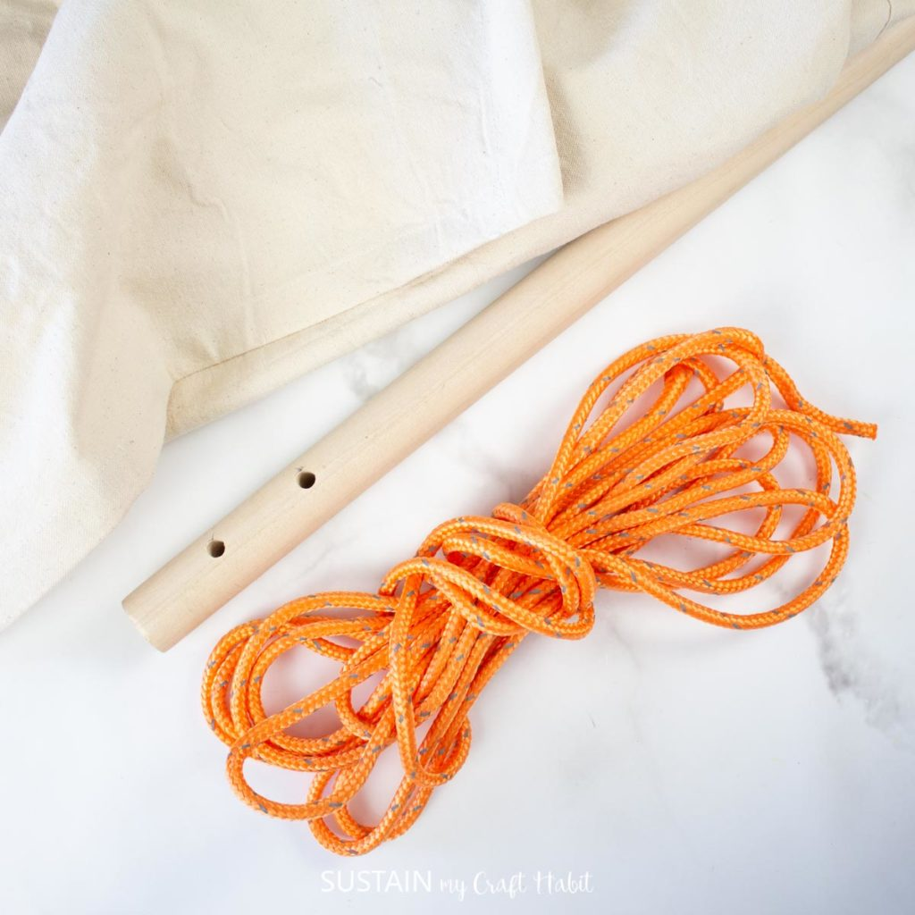 Two drilled holes in a wooden dowel next to orange rope and fabric.