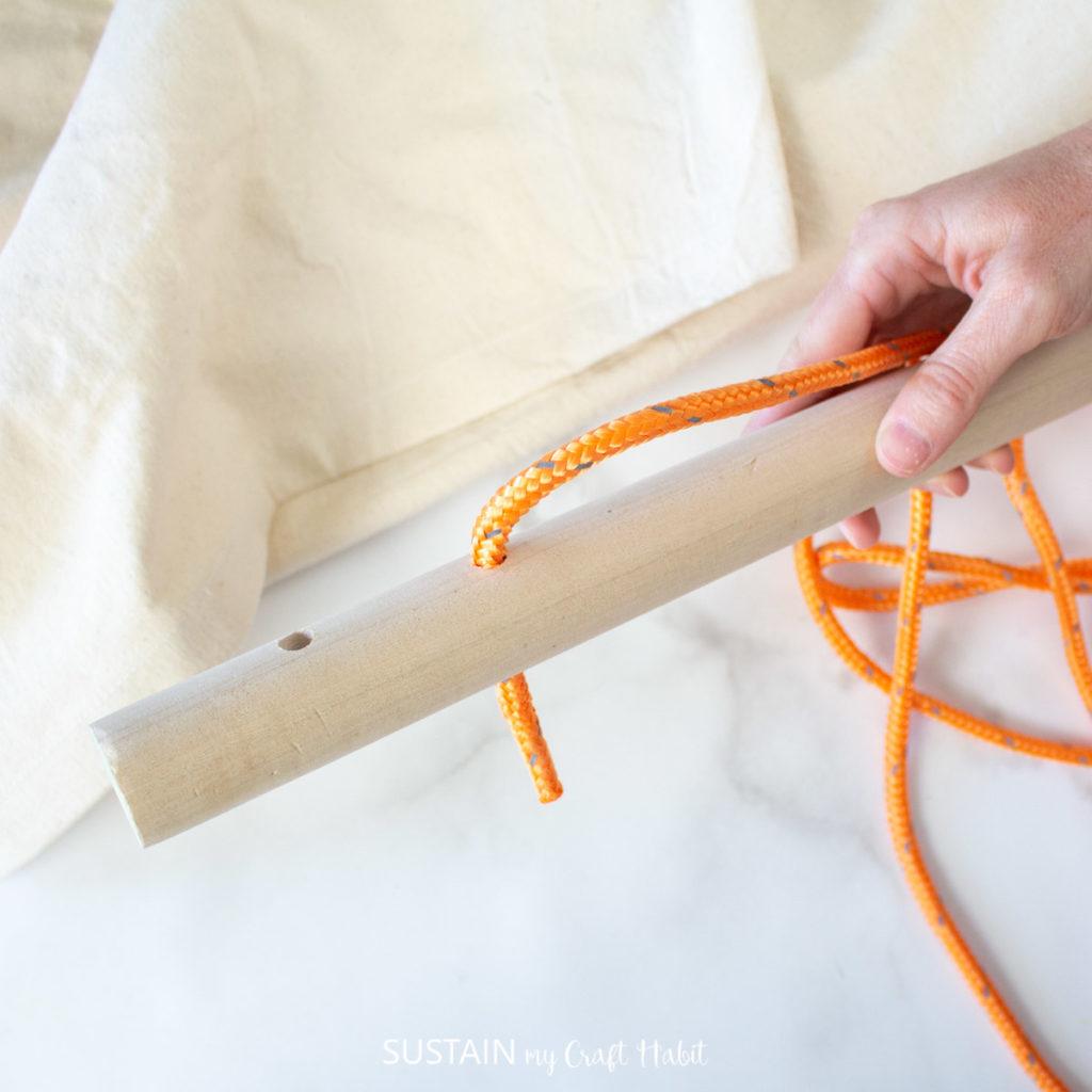 Threading orange rope into the wooden dowel.