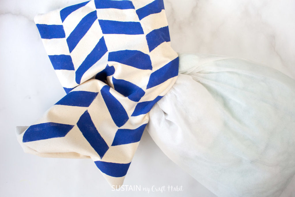 Putting a pillow inside the painted pillowcase.