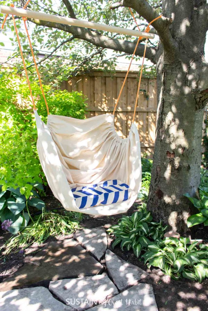 Fabric hammock chair hanging from a tree.