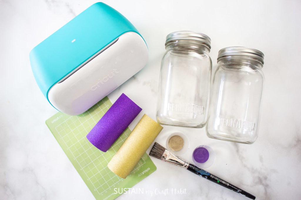 Materials needed to make decorative Eid jars including glass jars, Cricut machine, vinyl, paint and paint brushes.