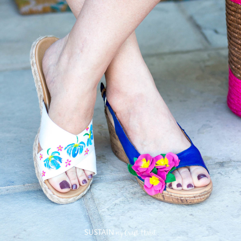 A woman wearing two different pretty painted sandals.