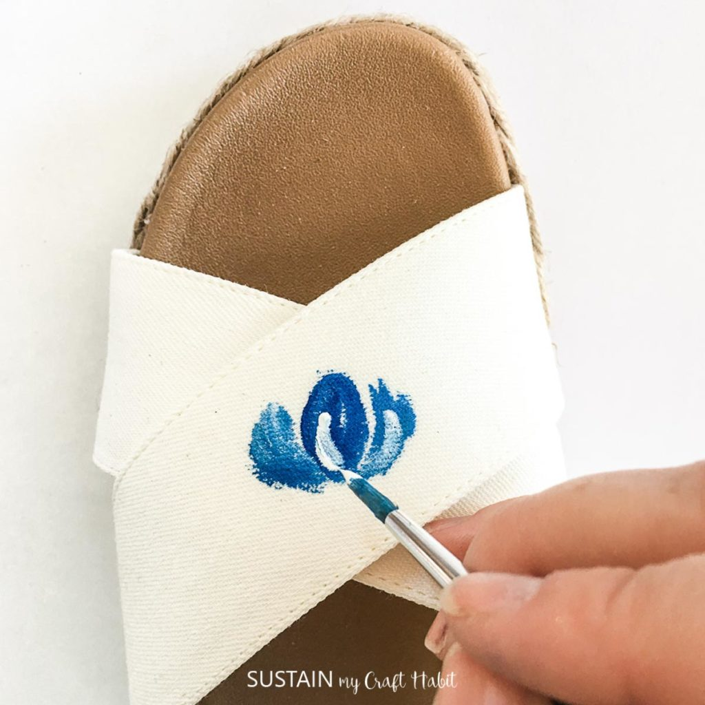 Painting more petals around the center petal on a white sandal.
