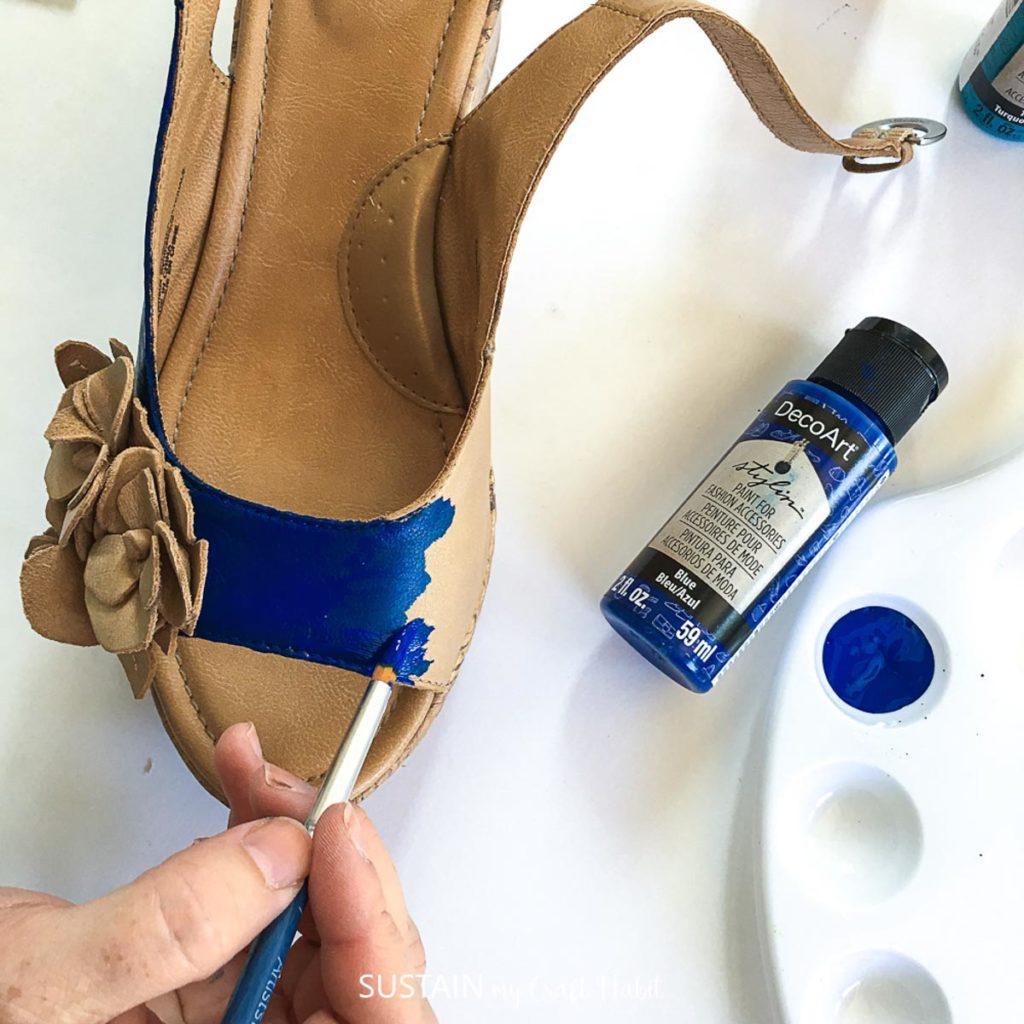 Painting a sandal blue.