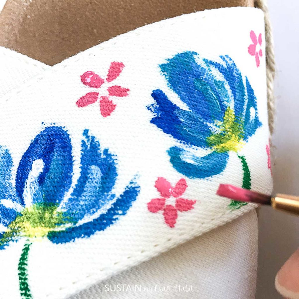 Painting small pink flowers onto the sandal.