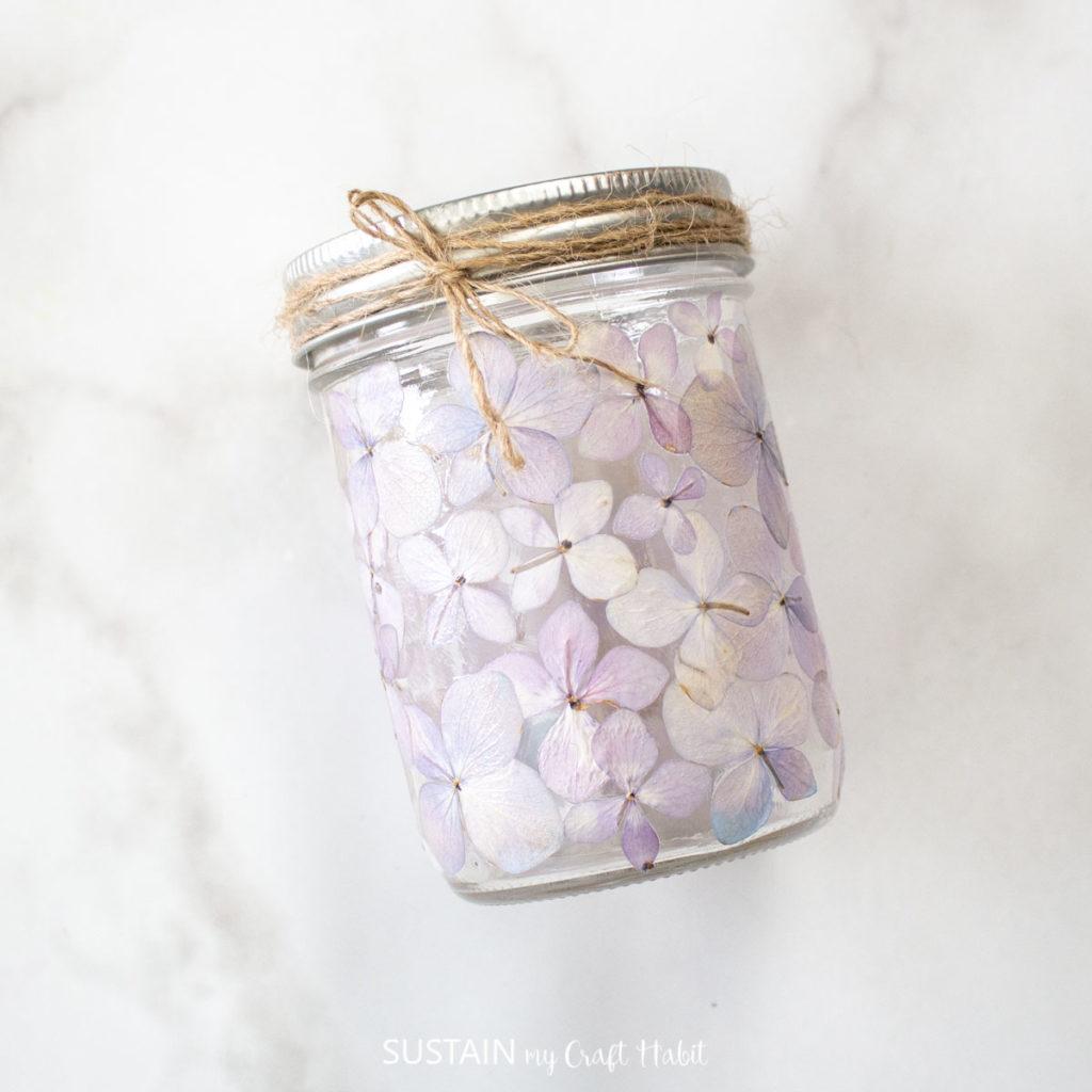 Purple painted pressed flower mason jar luminary.