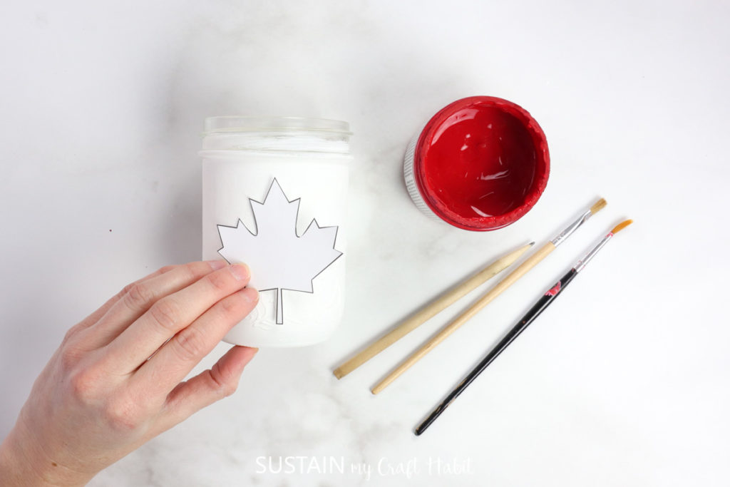 Holding a maple leaf cutout on a white jar.
