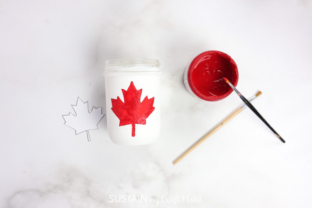 Painting a red maple leaf on a white jar.
