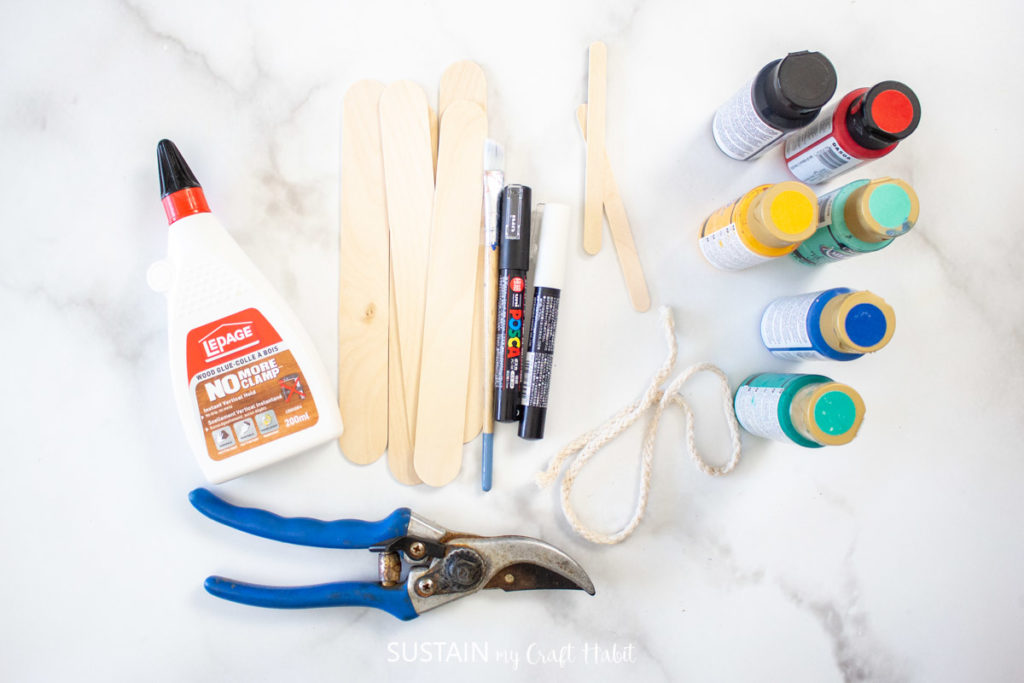 Materials needed to make a row house ornament including craft sticks, glue, paint, rope and clippers.