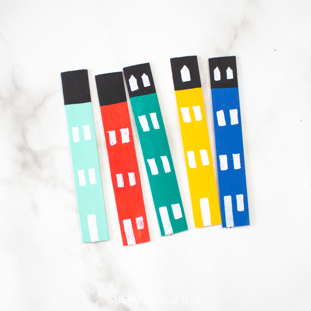 Painted popsicle sticks with little windows and doors.