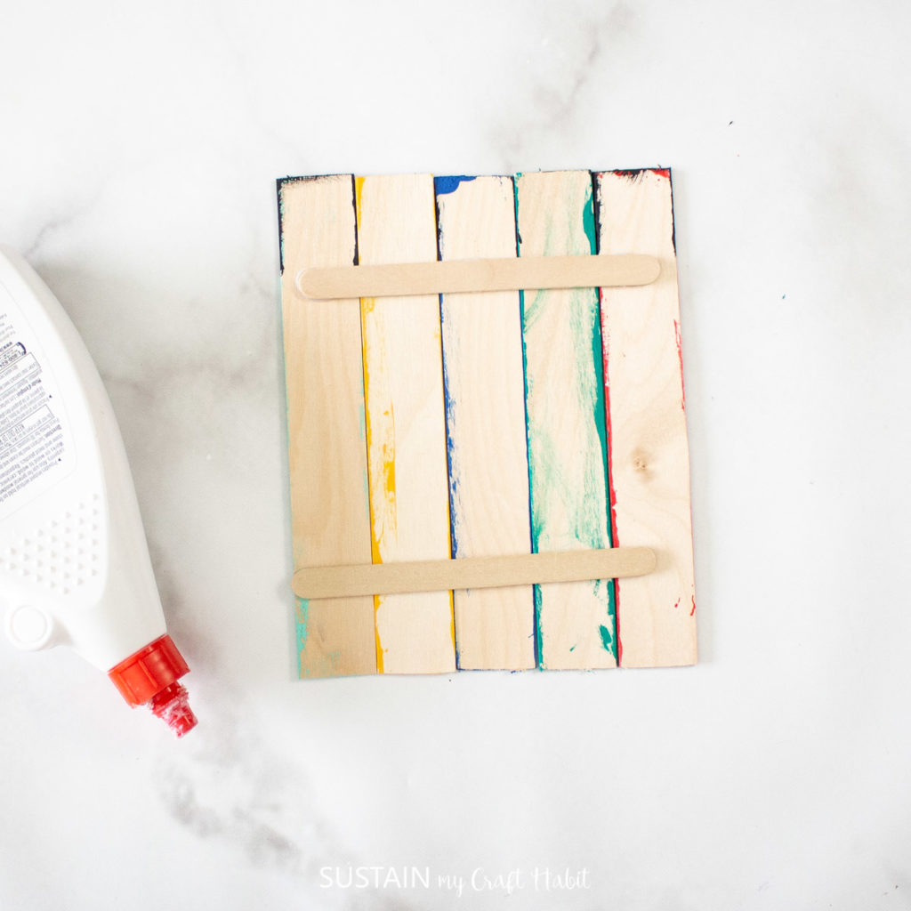 Gluing a smaller popsicle stick to the back of the large craft sticks.