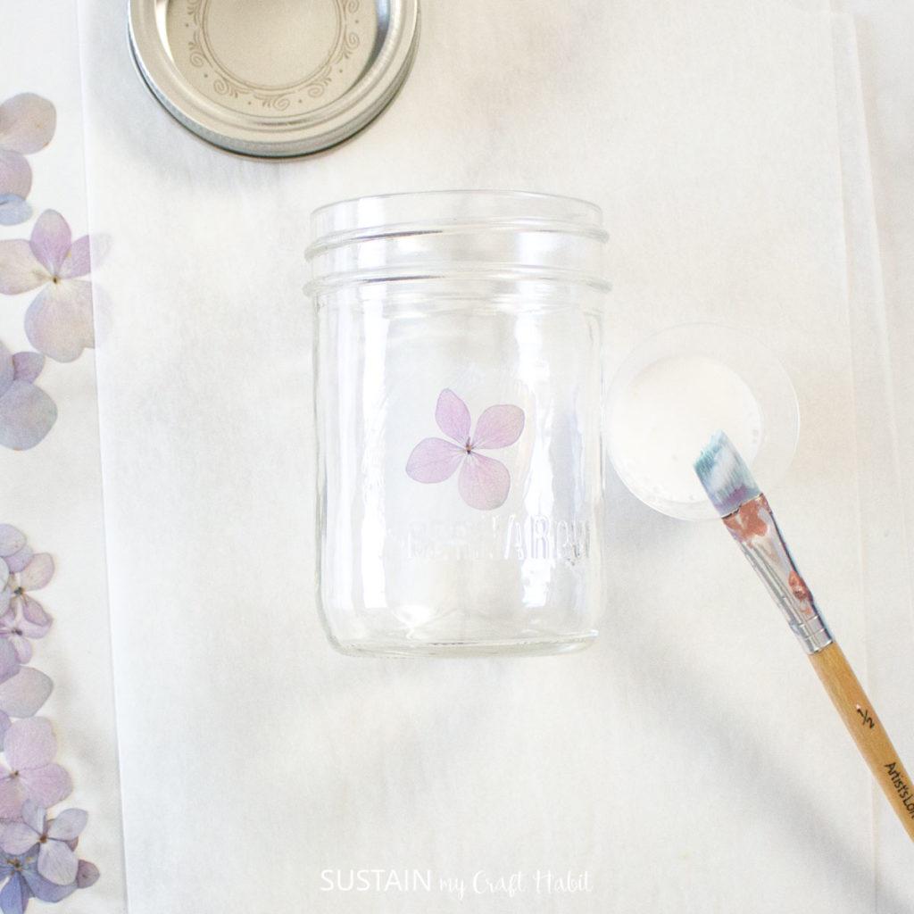 Pressing a hydrangea flower onto the mason jar.