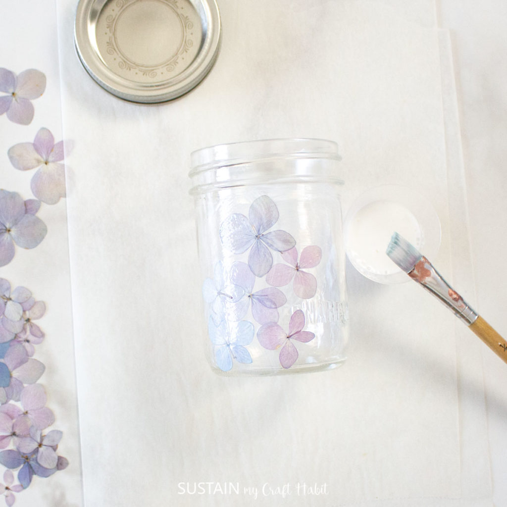 Covering the mason jar with hydrangea flowers.