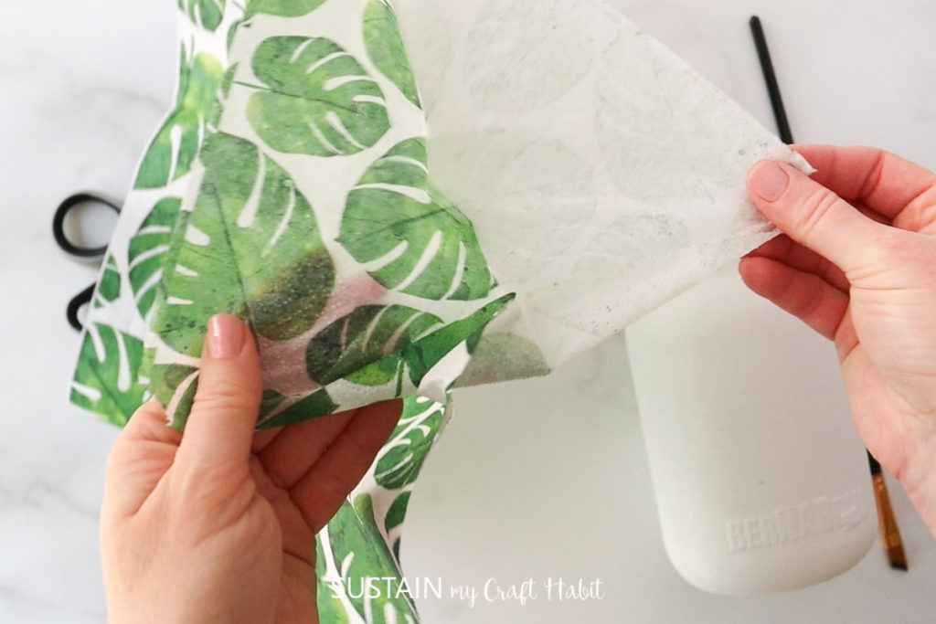 Removing an extra layer of paper from the napkin.