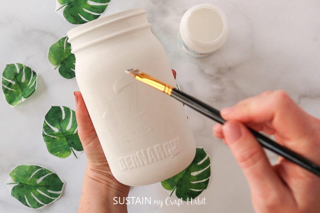 Adding a layer of Mod Podge onto the glass jar using a paint brush.